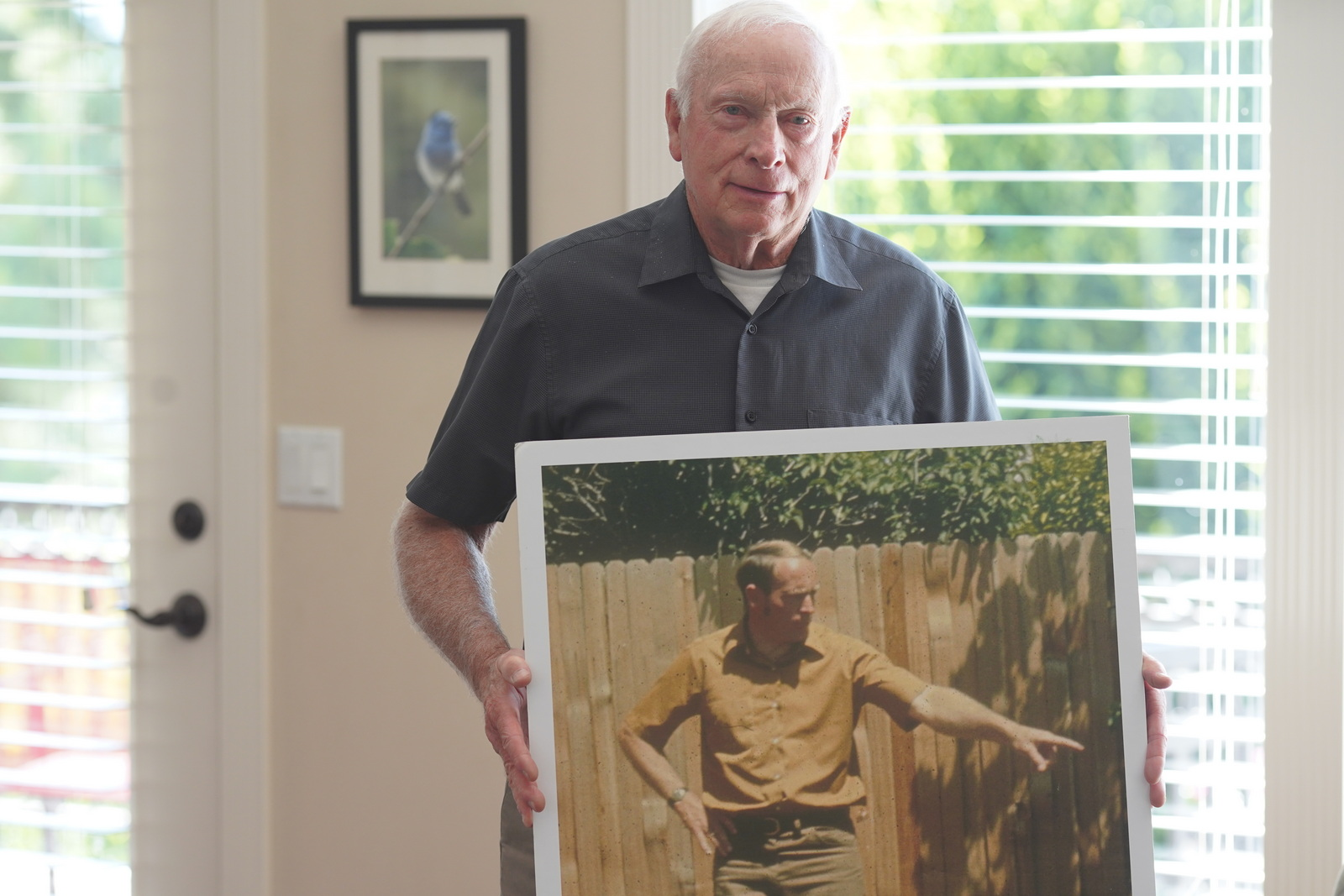 Vern holding a photo of him when he was younger