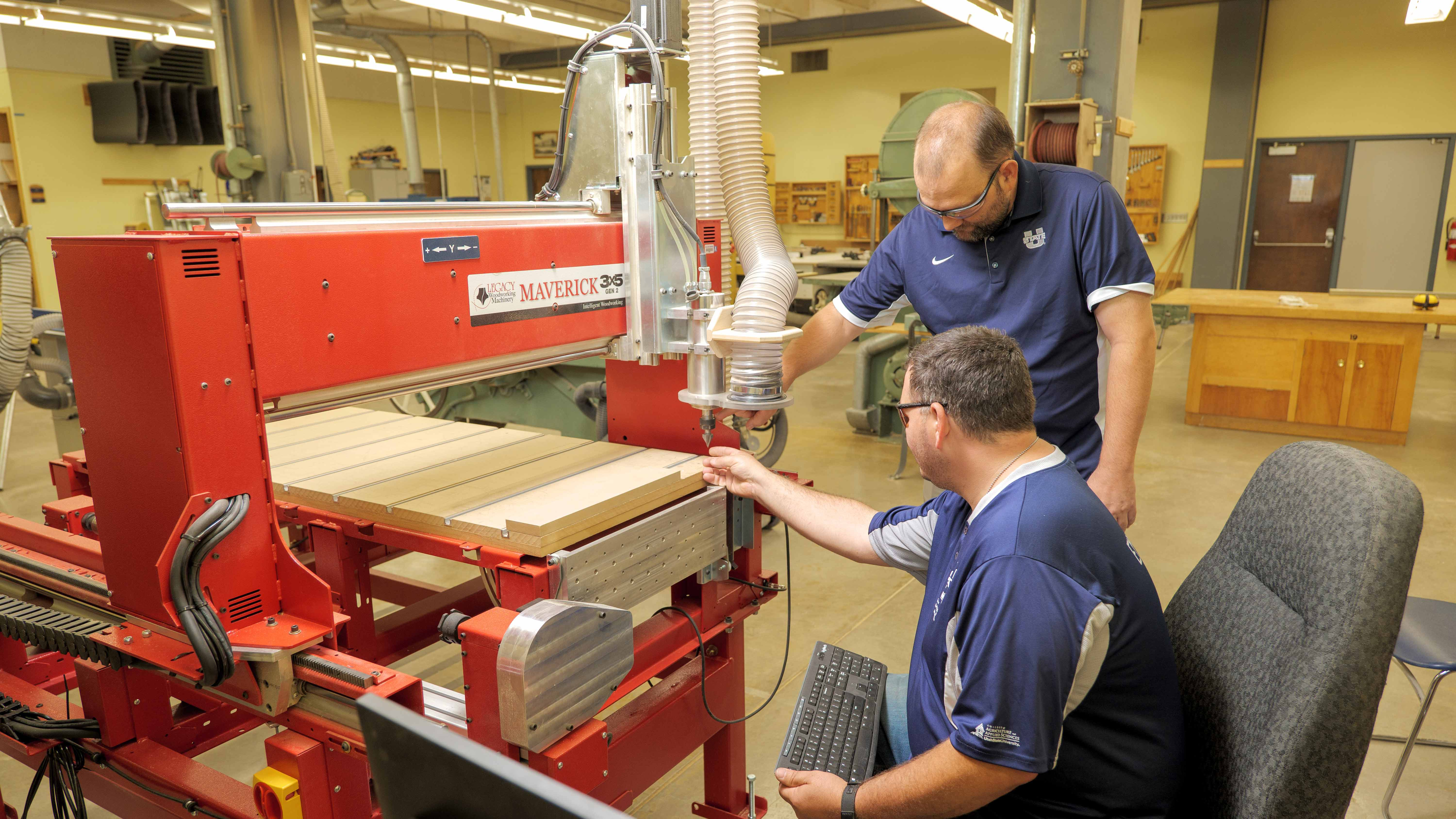Technology Systems student and professor working at the CNC router in the woods lab.