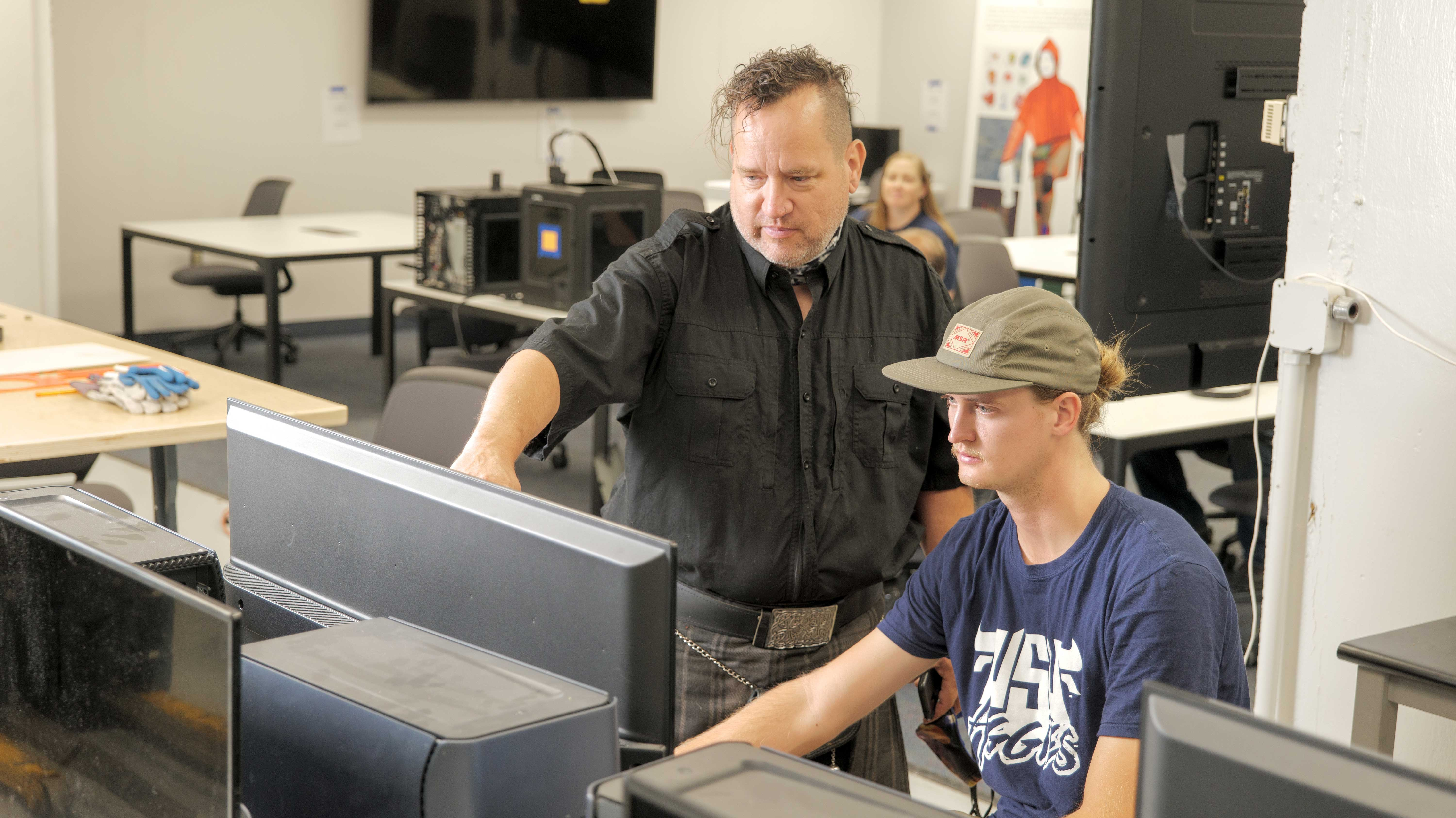 Technology Systems student and professor working in a computer lab.