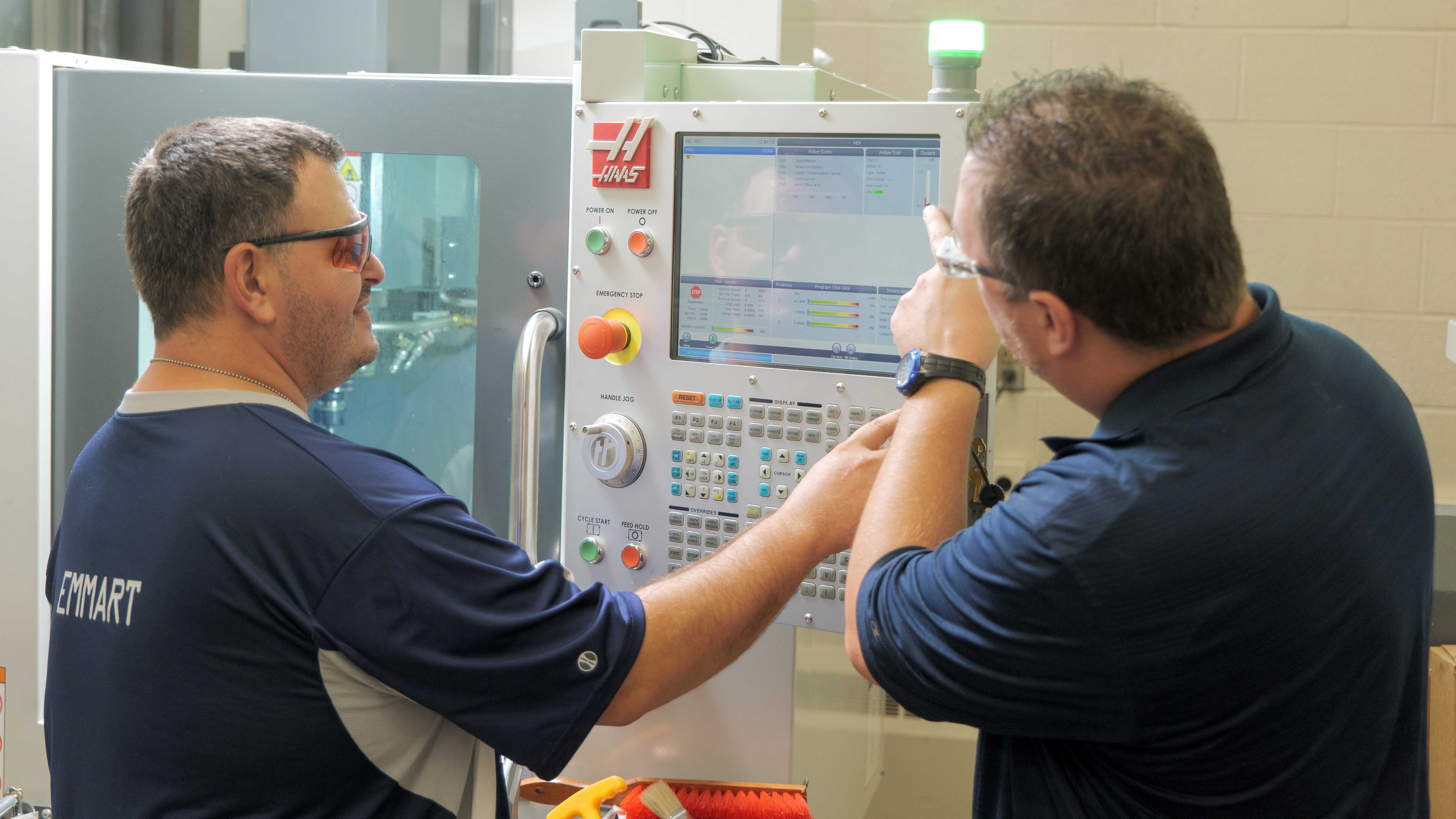 student and professor working at the CNC Mill in the machine lab.